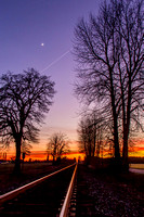 A Winter Sunset on a Railroad Track with the Moon and a Jet Trail